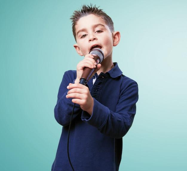 Niño adorable cantando con un micrófono