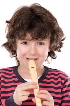 Niño adorable que juega la flauta en un fondo blanco excesivo