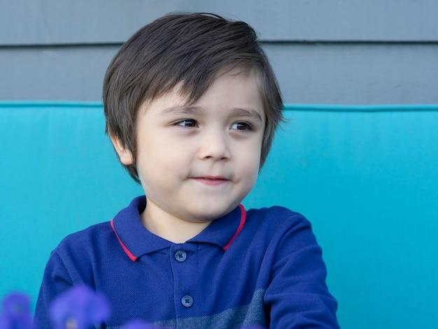 Niño adorable del retrato que mira hacia fuera con la cara sonriente