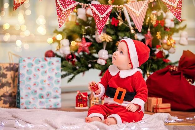 Un niño adorable vestido como santa claus juega cerca de un árbol de navidad decorado en la sala de estar.