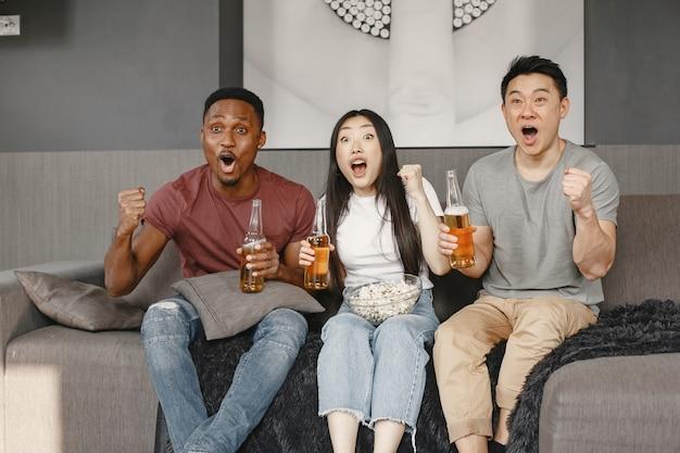 Niño africano y pareja asiática viendo fútbol, comiendo palomitas de maíz y bebiendo cerveza. amigos alentando a un equipo de fútbol.