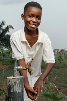 Niño africano sonriente lavándose las manos