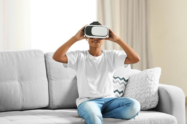 Niño afroamericano con gafas de realidad virtual y sentado en el sofá en una habitación
