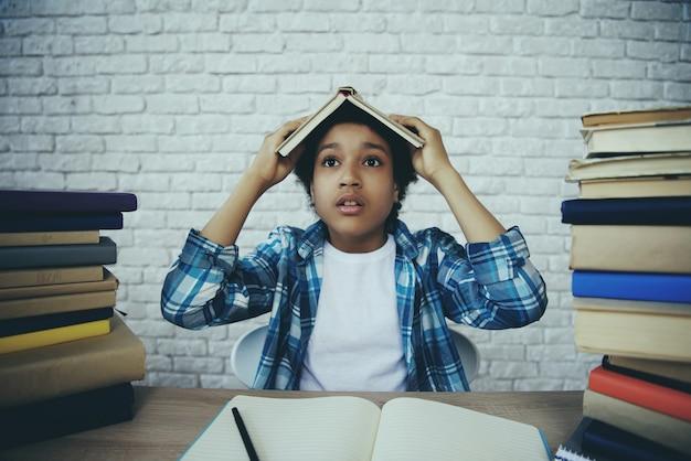 Niño afroamericano sostiene libro sobre la cabeza.