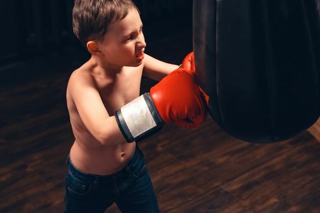 Niño agresivo en guantes de boxeo