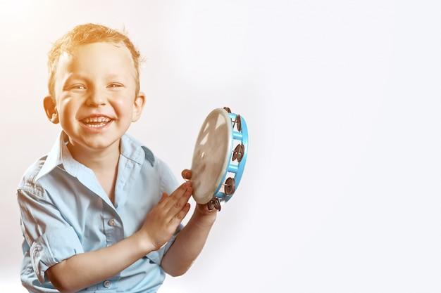 Un niño alegre en una camisa azul sosteniendo una pandereta y sonriendo