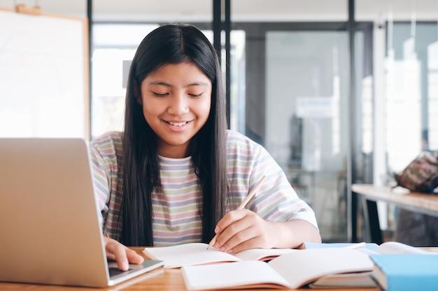 Niño alegre emocionado usando la computadora para el aprendizaje en línea. concepto de educación en línea y autoestudio y educación en el hogar.