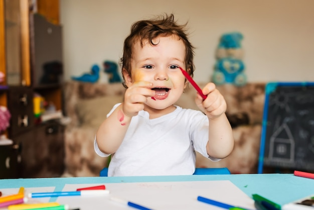 Un niño alegre y feliz dibuja con un rotulador en un álbum usando una variedad de herramientas de dibujo.