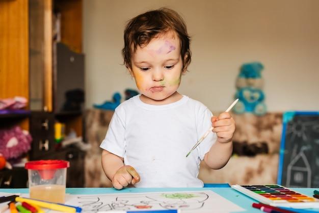 Niño alegre feliz dibujando con pincel en álbum usando una gran cantidad de herramientas de pintura.