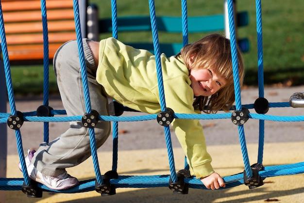 Niño alegre jugando en coloridos juegos en un parque