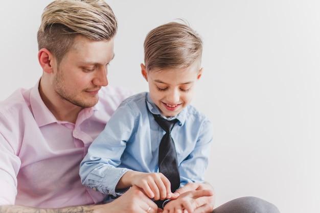 Niño alegre jugando con las manos de su padre
