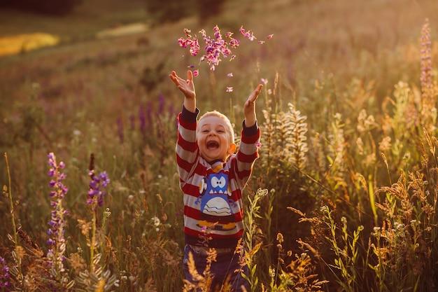 Niño alegre lanza pétalos posando en el campo de lavanda