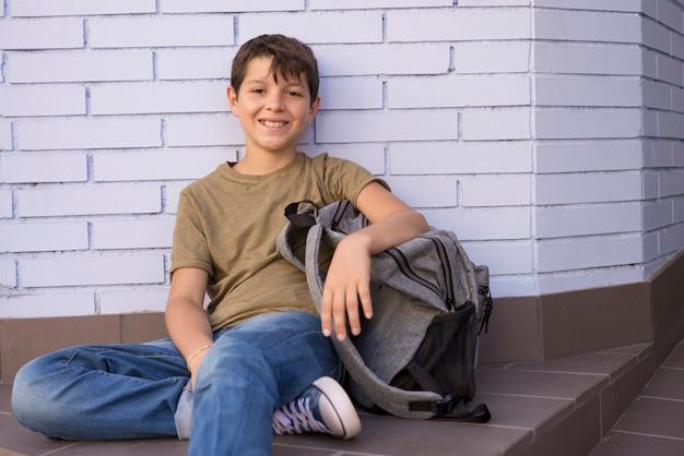 Niño alegre llevando su mochila