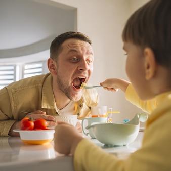 Niño alimentando a su padre hambriento