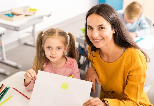 Niño de alto ángulo mostrando su dibujo con su maestra