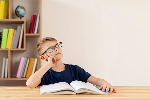 Niño de alto ángulo pensando en el libro leído