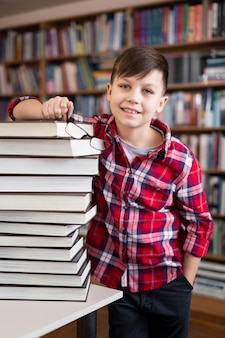 Niño de alto ángulo con pila de libros en la biblioteca