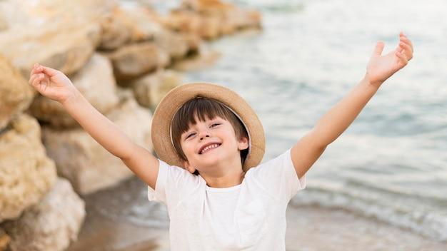 Niño de alto ángulo posando en la playa