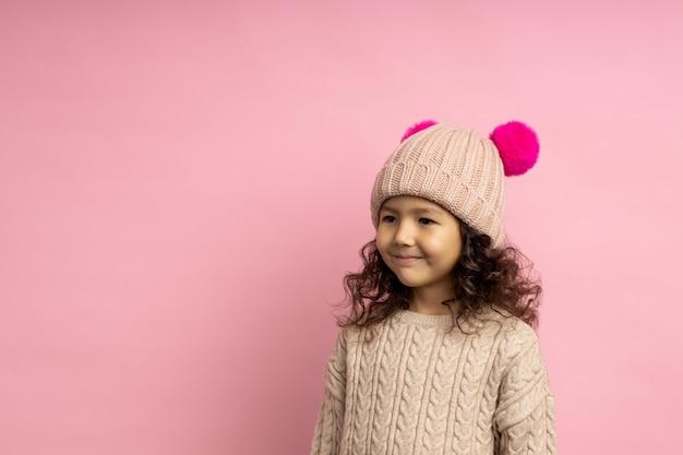 Niño amistoso con cabello rizado, vestido con suéter beige y gorro de punto con pompones, sonriendo mirando a un lado, de pie con espacio de copia. invierno, moda infantil.