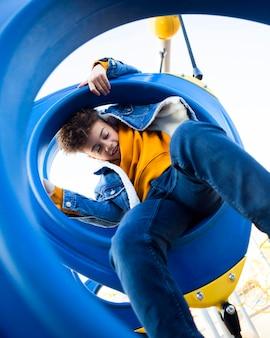 Niño de ángulo bajo divirtiéndose en el patio de recreo