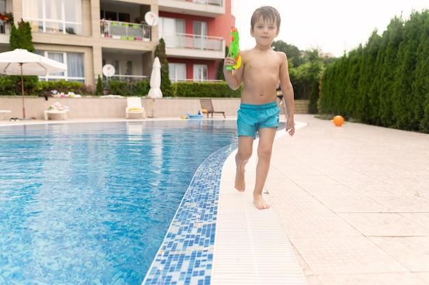 Niño de ángulo bajo con pistola de agua