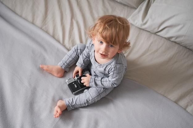 Niño de un año jugando en la cama con una cámara vieja, foto de estilo de vida