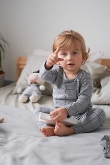 Niño de un año jugando en la cama con sus juguetes favoritos foto de estilo de vida