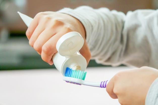 El niño aplica el cepillo de dientes y la crema dental en el fondo borroso