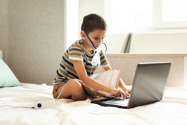 Un niño aprende lecciones caseras en una máscara de oxígeno con un nibulizador, una computadora portátil y un libro
