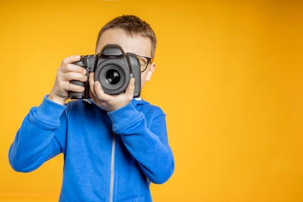 El niño aprende la profesión de fotógrafo.