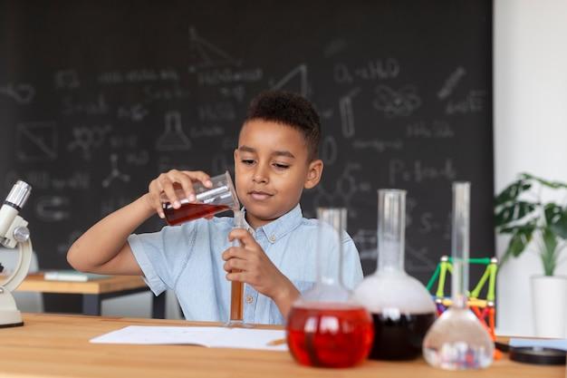 Niño aprendiendo más sobre química en clase.