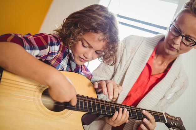 Niño aprendiendo a tocar la guitarra