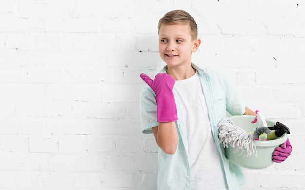Niño apuntando mientras sostiene productos de limpieza con espacio de copia