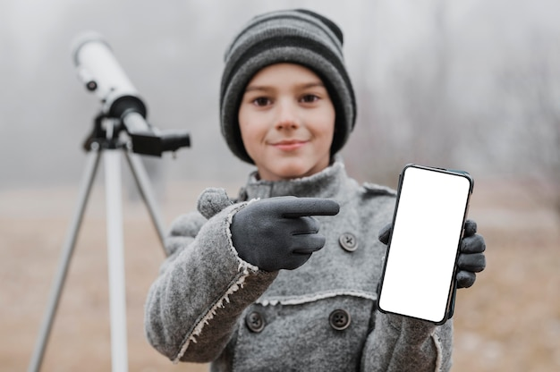Niño apuntando a un teléfono inteligente en blanco