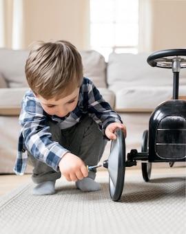 Niño arreglando sus ruedas desde el auto de carreras