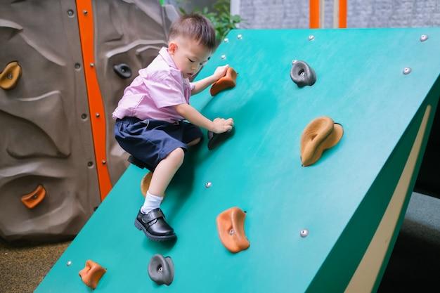 Niño asiático de 2 a 3 años que se divierte tratando de escalar rocas artificiales en el patio del patio de la escuela, little boy trepando por la pared de roca