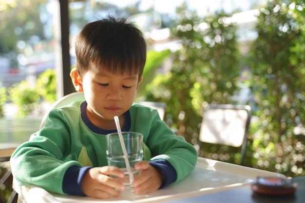 Niño asiático de 3 años bebiendo agua