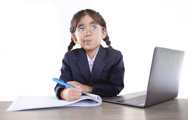 Niño asiático aprendiendo de la clase en línea con el portátil en la mesa en la pared blanca aislada