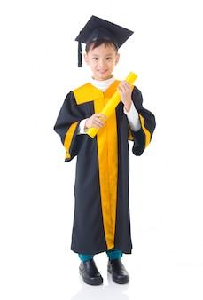 Niño asiático en bata de graduación