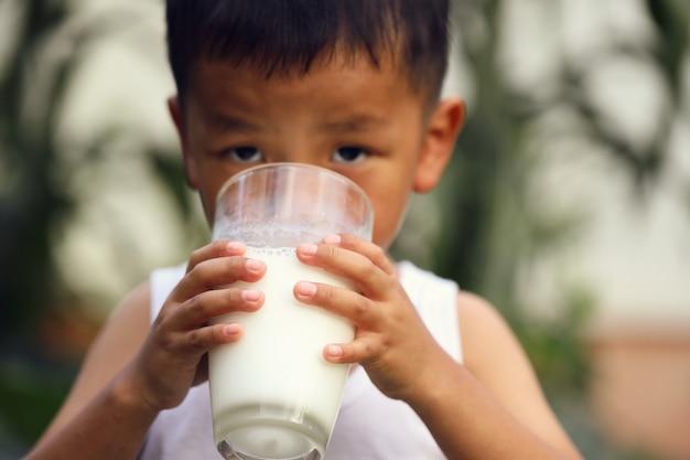 Un niño asiático está bebiendo leche de un vaso grande.