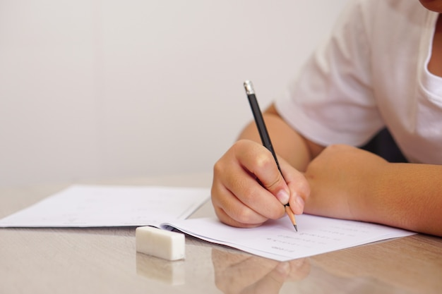 Un niño asiático con una camiseta blanca haciendo los deberes o escribiendo un cuaderno con lápiz sobre la mesa. concepto de educación y aprendizaje. Foto Premium