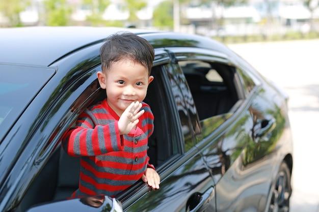 Niño asiático en coche sonriendo y mirando a cámara sentado en un asiento de coche diciendo adiós.