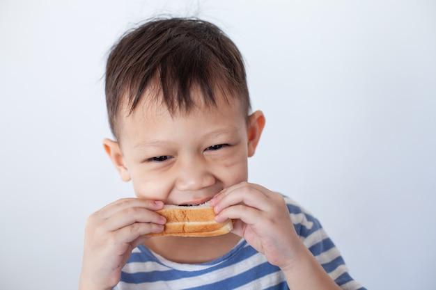 Niño asiático comiendo pan antes de ir a la escuela