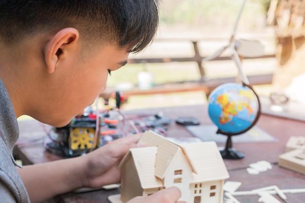 Niño asiático construyendo una casa de juguete o una casa de rompecabezas al aire libre cerca del globo