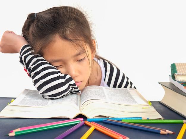 Un niño asiático duerme mientras lee un gran libro.