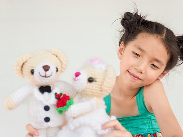 El niño asiático encantador está jugando las muñecas del oso de la boda