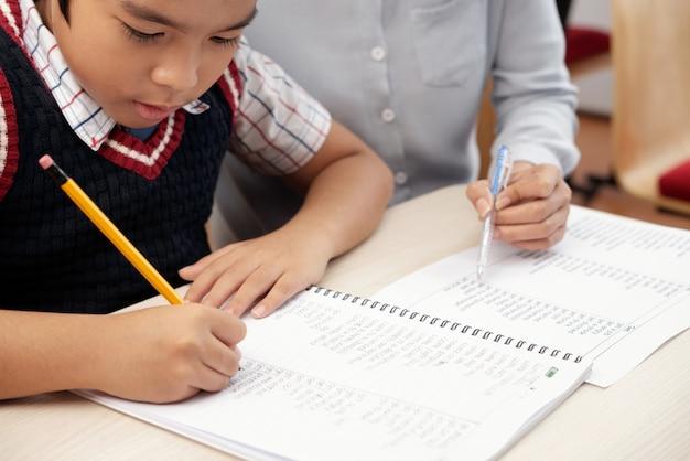 Niño asiático escribiendo en cuaderno y mujer irreconocible sentada y mirando
