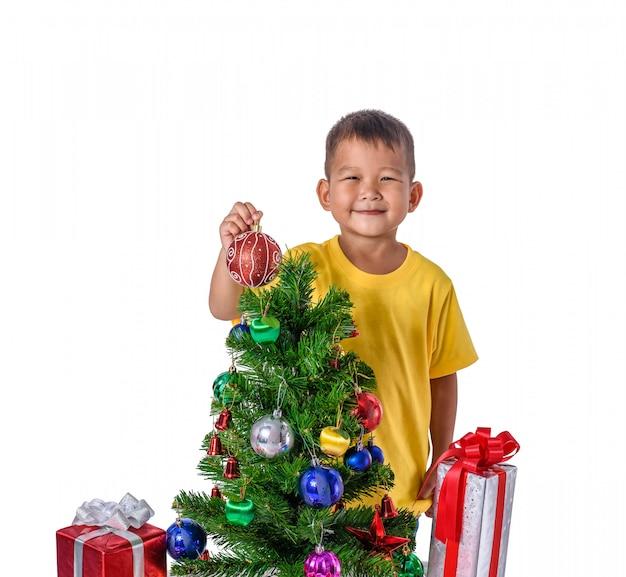 Niño asiático feliz que sostiene la bola roja para el árbol de navidad de la decoración. navidad o feliz año nuevo
