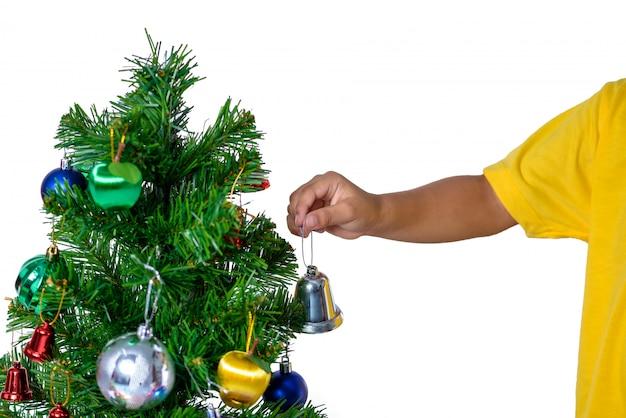 Niño asiático feliz que sostiene la pequeña campana para el árbol de navidad de la decoración. navidad o feliz año nuevo