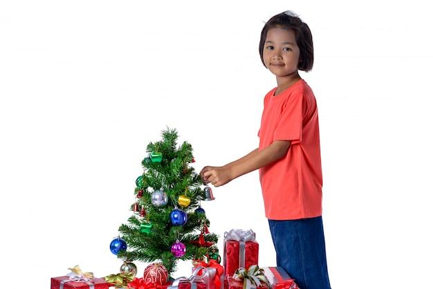 Niño asiático feliz que sostiene la pequeña campana para el árbol de navidad de la decoración.